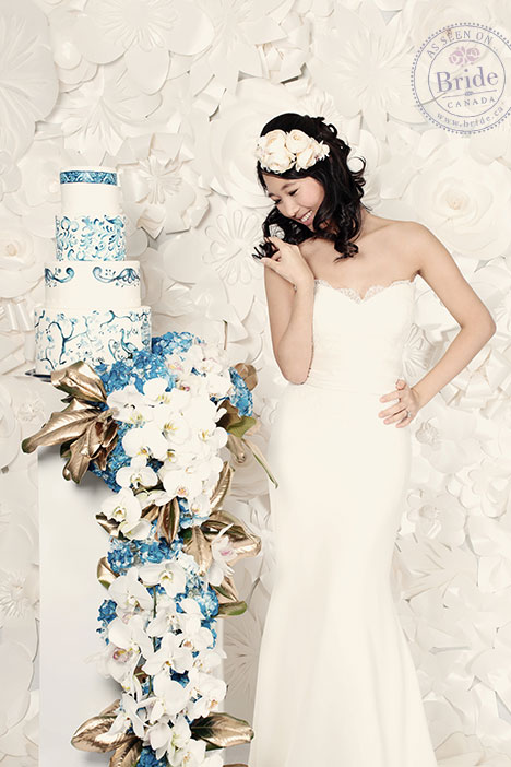 bride standing in front of white paper wall wearing soft by rosa clara sabia trumpet gown with lace bodice and floral headpiece.
