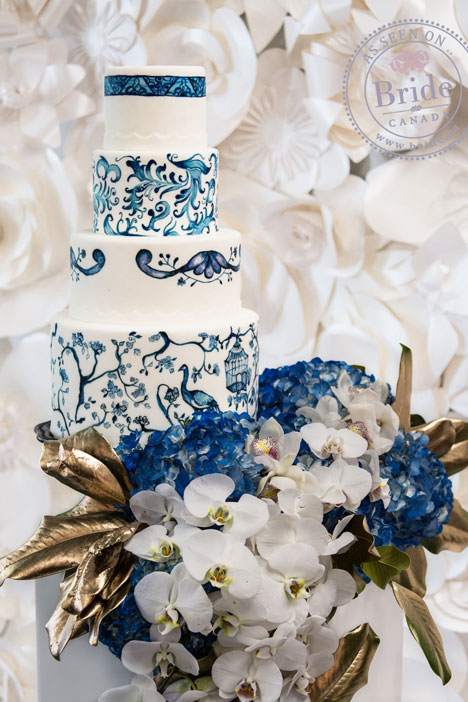 white and blue hand painted wedding cake with asian motif in front of a white paper flower wall with gold leaves, white and blue flowers.