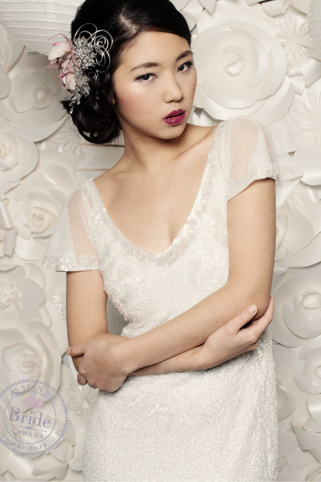 asian model wearing rosa clara soft ulises wedding dress in front of a white paper floral wall.