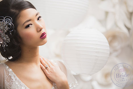 Close-up of model wearing ulises dress by soft by rosa clara, standing amidst white paper lanterns.