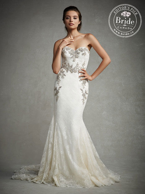 Model wearing Enzoani Jocelyn trumpet lace wedding dress with silver beaded and embroidered floral and leaf pattern on bodice and cascading down hips