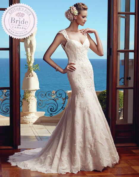 Model standing on a mediterranean terraza wearing a lace fitted trumpet wedding dress by Casablanca Bridal with sweetheart neckline and portrait lace sleeves.