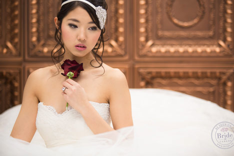 bride holding a red rose in a tulle and lace ballgown, crystal headpiece with ivory ribbon in her hair