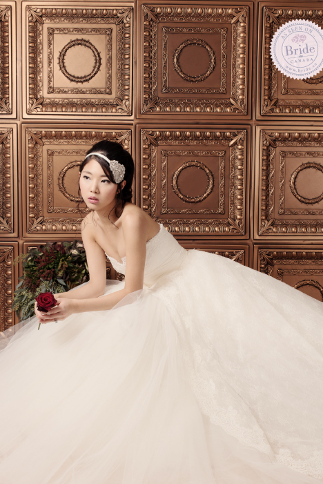 bride wearing Rosa Clara Camboya ball gown in front of a bronze wall, holding a red rose