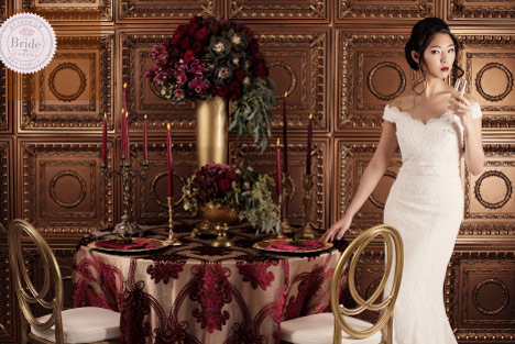 bride wearing trumpet off the shoulder lace wedding dress, standing beside opulent tablescape with scarlet flowers and red candelabras.