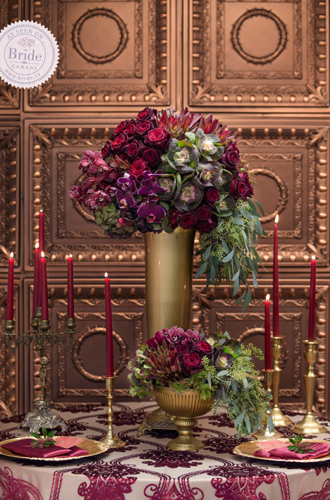 red and gold tablescape with tall gold urn, succulents, and hanging leaves. gold chargers and candelabras with red candles in front of a copper wall.