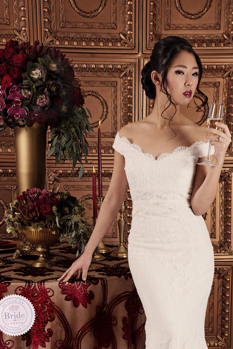 bride wearing off the shoulder lace trumpet wedding dress, holding a glass of champagne beside an opulent table