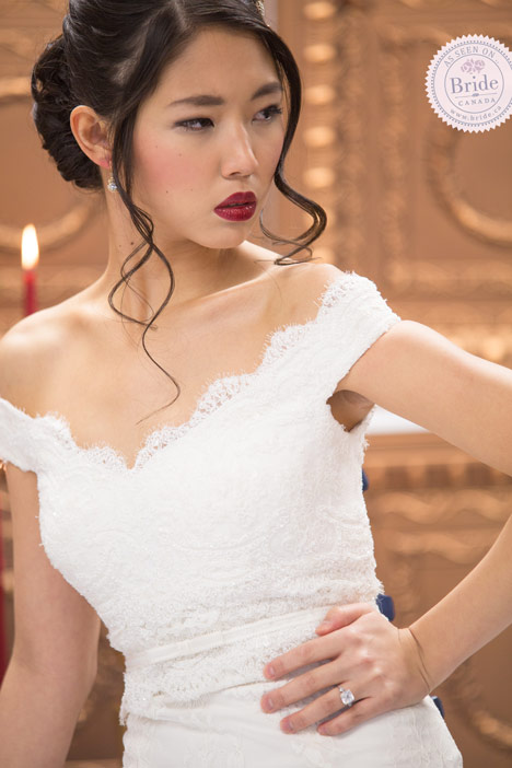 bride wearing rosa clara santel wedding dress. close up of lace off the shoulder bodice and low updo wedding hairstyle