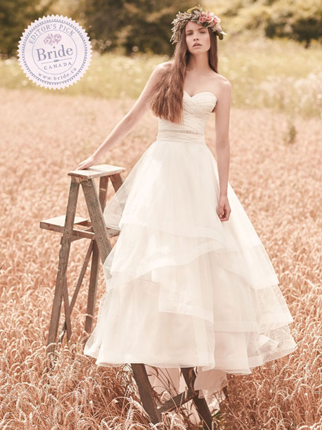 model in field on ladder wearing Mikaella 2070 ball gown wedding dress tulle layered skirt and ruched bodice