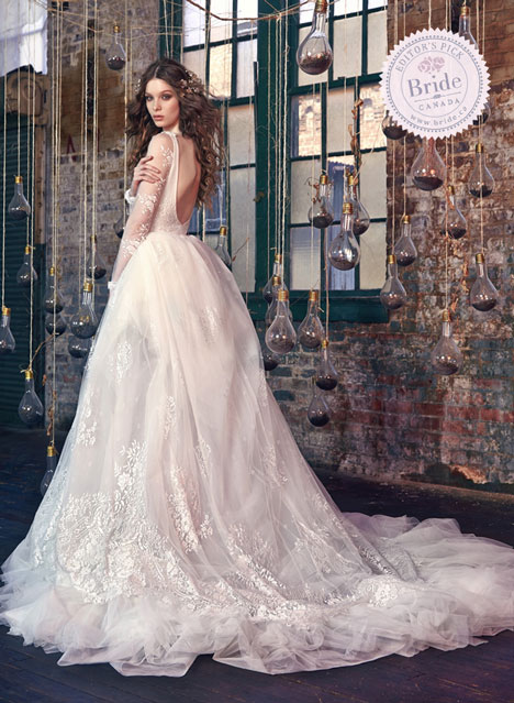 Model wearing galia lahav snow white ball gown in room with hanging vintage light bulbs and exposed brick walls