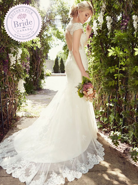 Model wearing Essense of Australia D1845 fit and flare lace wedding dress with open back in a garden on a tree lined path