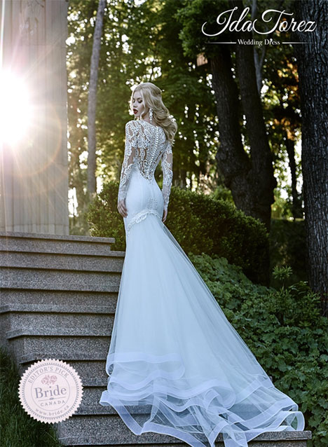 Model sitting on the end of a chaise lounge wearing Maggie Sottero Verina sheath beaded lace wedding dress with sheer illusion bateau neckline and fitted sleeves.