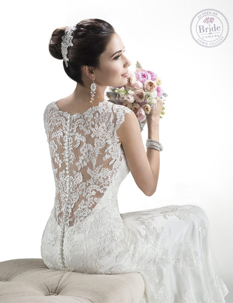 Model wearing Maggie Sottero Melanie trumpet gown with lace-covered low back.
