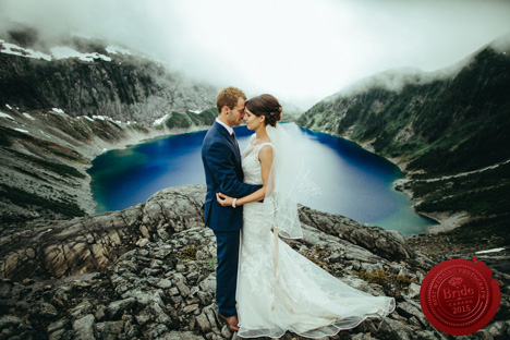 bride and groom overlooking mountain lake canyon