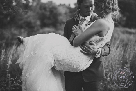 romantic image of groom carrying his bride in a field with tall grass