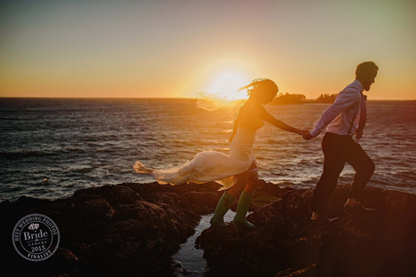 westcoast wedding of bride and goom oceanside on rocks sun setting and bride wearing wellies