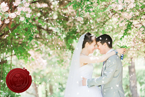 bride and groom standing under cherry blossom trees with petals falling all around