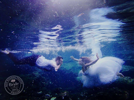 underwater wedding photo bride and groom swimming towards one another