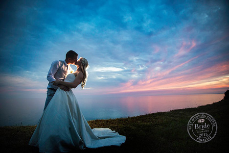 bride and groom kiss lakeside at dusk with cotton candy skies