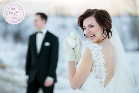 winter wedding photography playful bride with mittens and snowball groom in distance