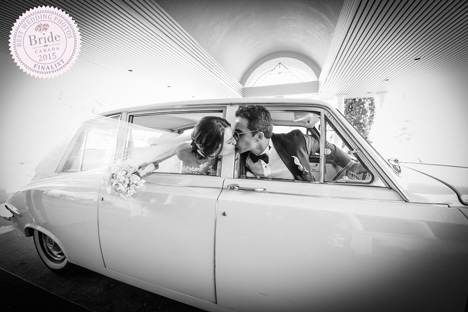 bride and groom stretching from front and back seat to kiss in vintage car