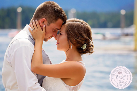 closeup of bride and groom standing in front of water snuggling nose to nose