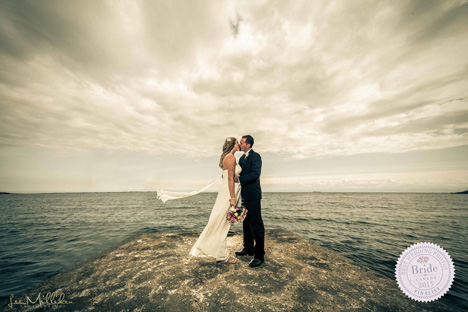 bride and groom standing in front of ocean with stormy skies and sweeping clouds