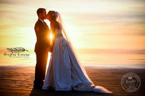 sunset photo of bride and groom beside ocean at low tide with sun peaking through couple's kiss