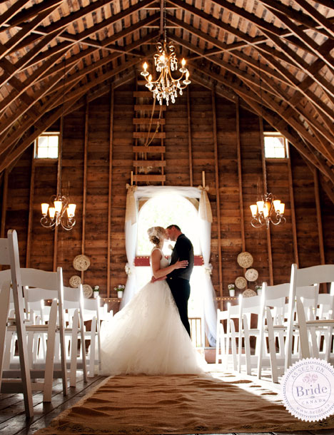 Bride and Groom kissing in a barn set up for a wedding ceremony