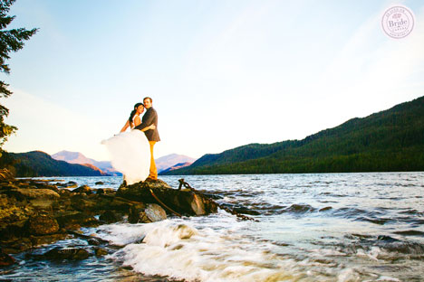 bride and groom standing on rocks at rivers edge with mountains in the background at sunset