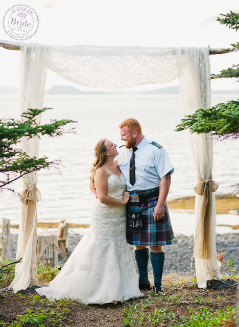 Bride and groom standing in front of altar at outdoor maritime wedding ceremony. Bridal party photos.