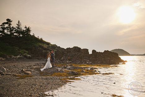 bride and groom standing on rocky beach beside ocean and cliffs at Newfoundland wedding