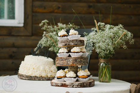 log cupcake stand and small white buttercream wedding cake with bride and groom cutting the cake.