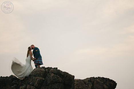 bride and groom on cliff with open sky and dress floating in the wind.