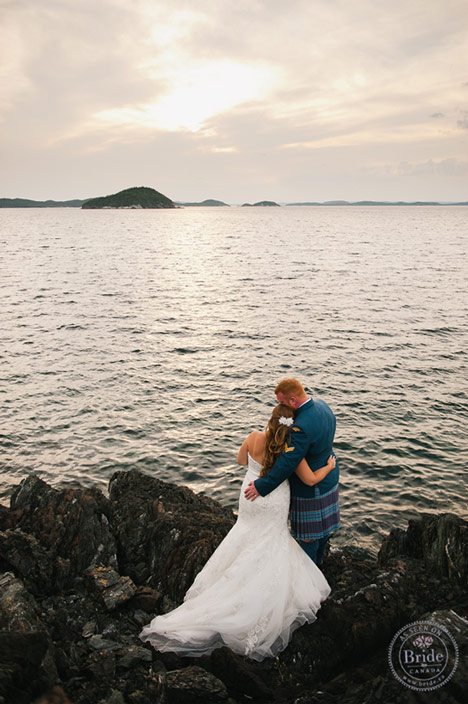 bride and groom on rocks beside ocean with sun setting.