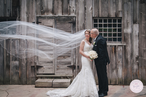 bride with windswept veil and groom in front of wooden historic building