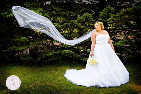 bride in tulle ballgown and ruched bodice with cathedral veil floating in the wind