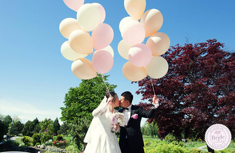 A bride and groom holding balloons and kissing outdoors at their wedding at Quilchena Golf Country Club.