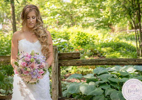 Bride in lace wedding dress by Melissa Gentile holding a pastel bouquet