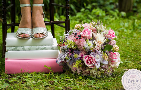 Beauty shot. Silver high heels on stacked books with pastel bouquet.