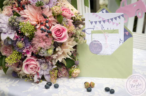 Pastel wedding theme with light green, light purple, and light pink. Bouquet, invitations, and welcome sign.