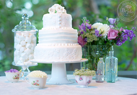 White fondant wedding cake with pearls and sugar flowers with vintage vases