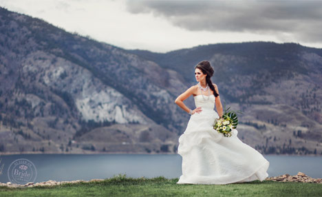bride wearing monique lhuillier bellflower standing beside Skaha Lake at Painted Rock Estate Winery