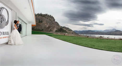 Bride and groom at Painted Rock Estate Winery with view of Skaha Lake
