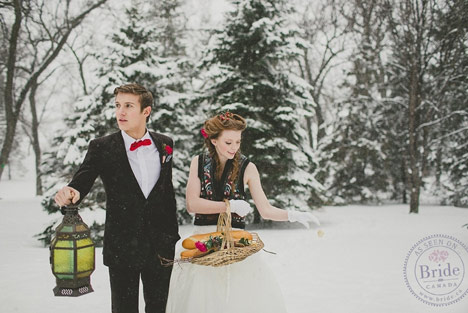 A bride and groom walking in snow covered trees with lantern and basket of bread