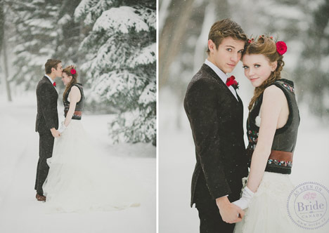 Bride in a ballgown and vest with groom standing in snowy trees. Groom kissing her forehead.